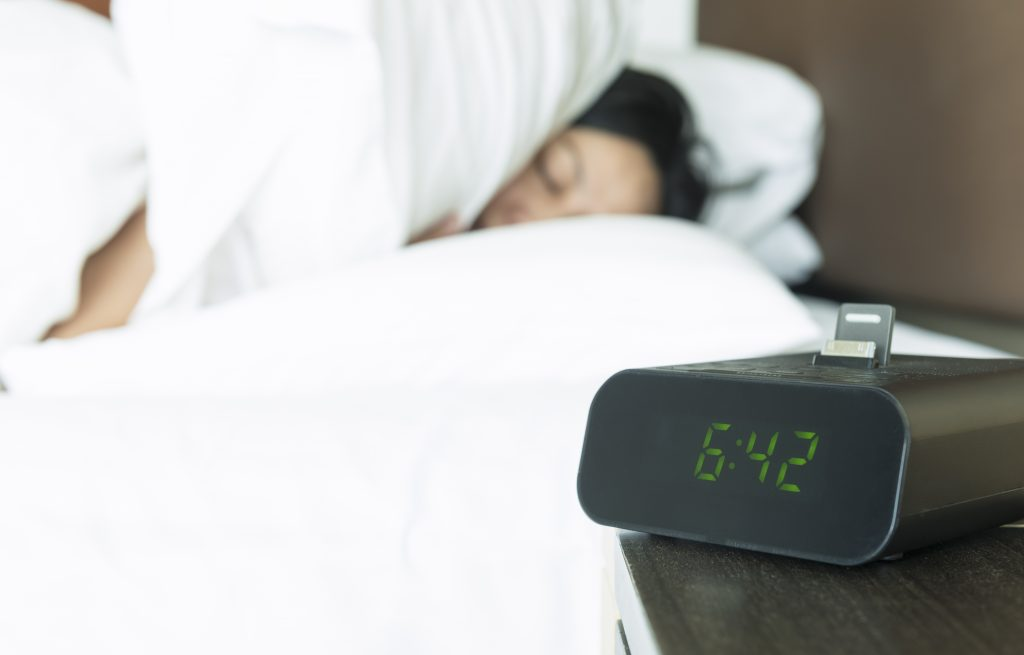 A Woman Sleeping Beside a Digital Alarm Clock