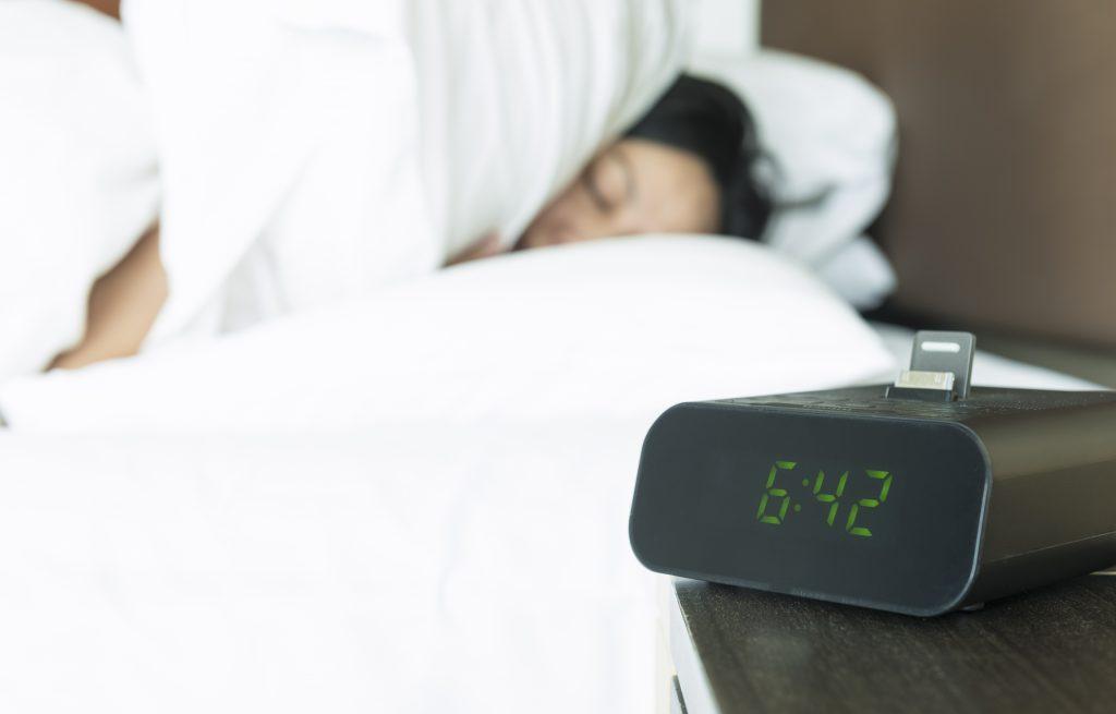 A Woman Sleeping Beside a Digital Alarm Clock
