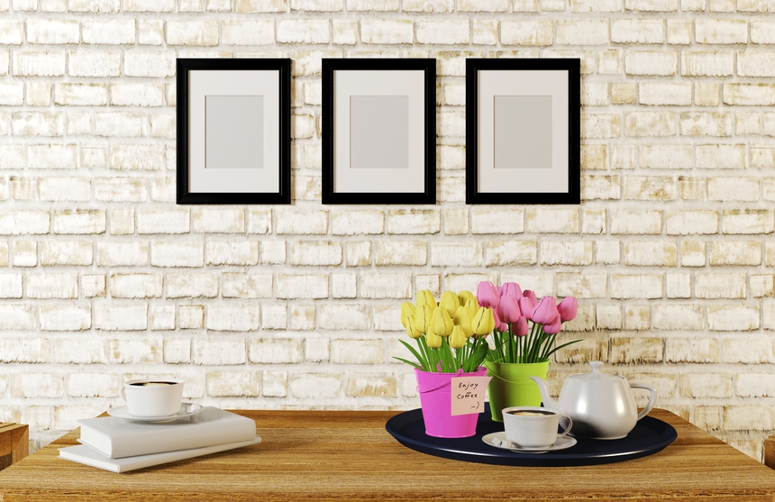 Coffee on table in white room decorated with frames