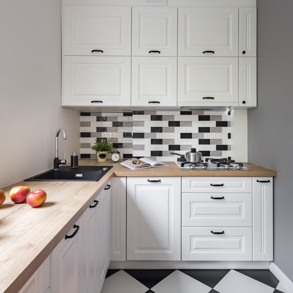 Small kitchen with classic white furniture and modern floor tiles