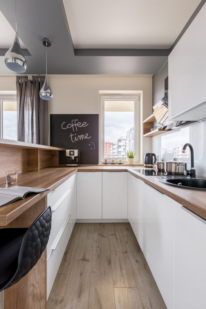 Modern kitchen with wooden worktop, white unit and blackboard