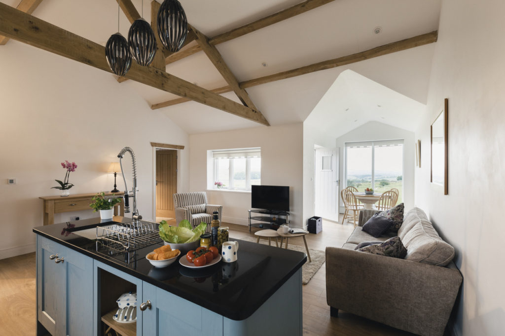 A wide-view shot of a modern living room and kitchen in Northeastern England.