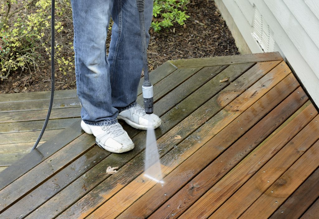 Man using power washer to clean dirt off of cedar deck.