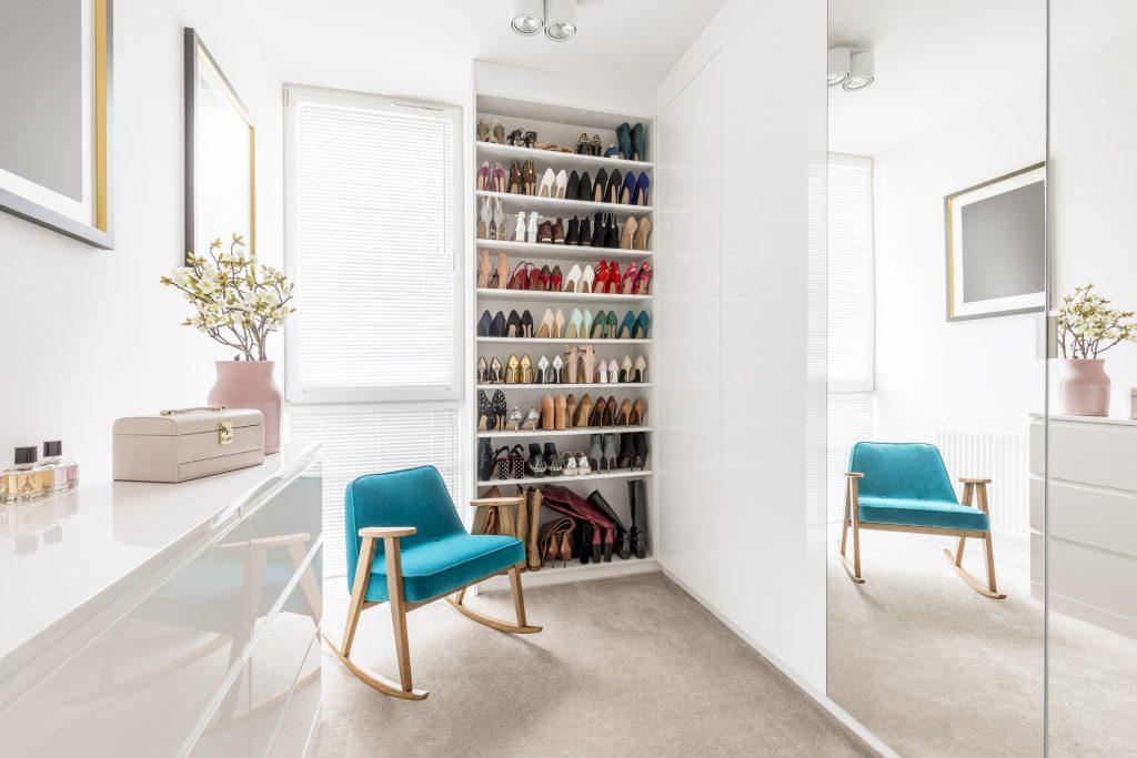 Dreamy feminine wardrobe with white furniture, big mirror, shoe closet, beige carpet, blue retro armchair and pastel pink accessories